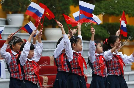 Vietnamese children wave Russian and Vietnamese flags prior to the arrival of Prime Minister Dmitri Medvedev to a welcoming ceremony at the Presidential Palace in Hanoi, Vietnam, 19 Novemeber 2018.
