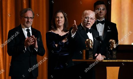 Kathleen Kennedy, Frank Marshall, Steven Spielberg. Producer Frank Marshall, right, addresses the audience as he and his wife Kathleen Kennedy, second from left, accept the Irving G. Thalberg Memorial Award during the 2018 Governors Awards at The Ray Dolby Ballroom, in Los Angeles. Looking on at far left is presenter Steven Spielberg