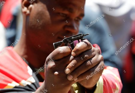 A member of the Economic Freedom Fighters (EFF) holds a miniature toy weapon outside the venue where Public Enterprises Minister Pravin Gordhan appears at the judicial commission of inquiry into state capture in Johannesburg, South Africa. . Gordhan is expected to reveal details surrounding former president Jacob Zuma's trillion-rand nuclear procurement campaign as well as other corruption practices