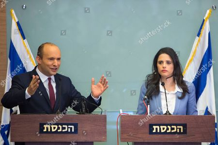 Israeli Education Minister Naftali Bennett, left, and Israeli Justice Minister Ayelet Shaked gesture as they speak during a press conference at the Knesset, Israel's parliament in Jerusalem, . Bennett, a senior coalition partner in Israel's government says he will not resign, averting early elections for now