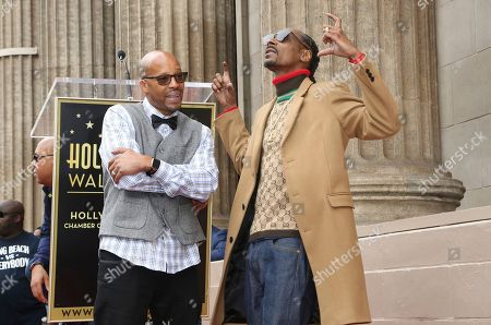 Snoop Dogg, Warren G. Rapper Snoop Dogg, right, poses atop his new star on the Hollywood Walk of Fame with rapper Warren G, in Los Angeles