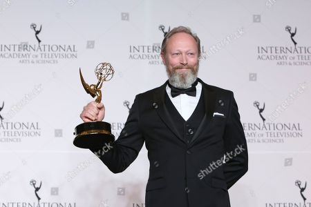 Stock Picture of Lars Mikkelsen holds his award for Best Performance by an Actor during the 46th International Emmy Awards gala in New York City