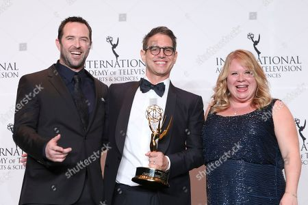 Sullivan Stapleton, Greg Berlanti, Julie Plec. Sullivan Stapleton, left, and US television producer Julie Plec, right, poses with writer Greg Berlanti and his Founders Award during the 46th International Emmy Awards gala in New York City Monday, Nov.19, 2018