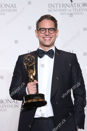 Greg Berlanti poses with his Founders Award during the 46th International Emmy Awards gala in New York City