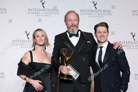 Stock Image of Mary Stuart Masterson, Lars Mikkelsen, Benjamin McKenzie. Actress Mary Stuart Masterson, actor Lars Mikkelsen, center, and actor Benjamin McKenzie pose in the pressroom with Danish who won the award for Best Performance by an Actor during the 46th International Emmy Awards gala in New York City
