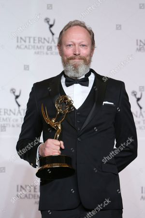Stock Photo of Lars Mikkelsen holds his award for Best Performance by an Actor during the 46th International Emmy Awards gala in New York City