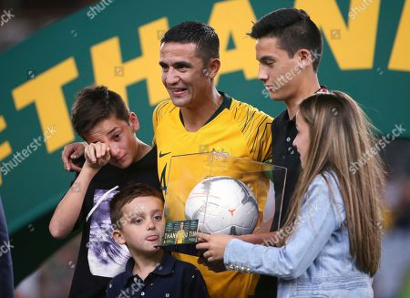 Australia's Tim Cahill, center, celebrates with his children, Kyah, second right, Shae, left, Sienna, right, and Cruz, after playing his final game for Australia following their win over Lebanon in an international soccer friendly in Sydney