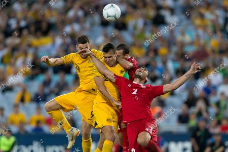 Lebanon player Kasssem El Zein (2) Australian defender Trent Sainsbury (20) and Australian forward Tomi Juric (9) all try to head the ball from a corner at the international soccer match between Australia and Lebanon at ANZ Stadium in NSW, Australia.