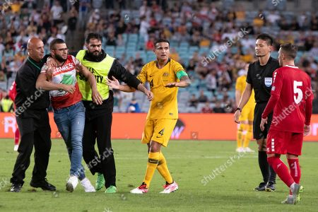 Lebanese fans invade the pitch near Australian forward Tim Cahill (4) at the international soccer match between Australia and Lebanon at ANZ Stadium in NSW, Australia.