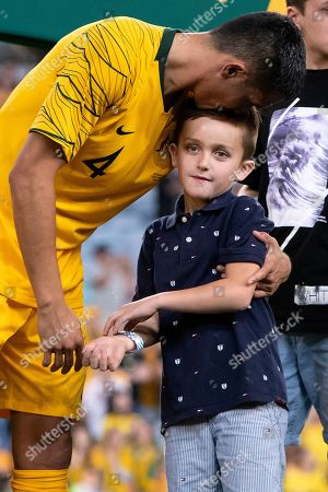 Stock Image of An emotional Australian forward Tim Cahill (4) with his family after his last game at the international soccer match between Australia and Lebanon at ANZ Stadium in NSW, Australia.