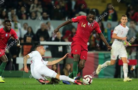 Poland's Jacek Goralski, left, vies for the ball with Portugal's William Carvalho during the UEFA Nations League soccer match between Portugal and Poland at the D. Afonso Henriques stadium in Guimaraes, Portugal