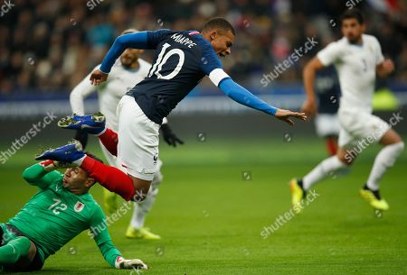 France's Kylian Mbappe jumps over Uruguay goalkeeper Martin Campana during the international friendly soccer match between France and Uruguay at the Stade de France stadium in Saint-Denis, outside Paris, Tuesday, Nov.20, 2018