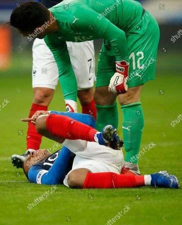 France's Kylian Mbappe is comforted by Uruguay goalkeeper Martin Campana, right, during the international friendly soccer match between France and Uruguay at the Stade de France stadium in Saint-Denis, outside Paris, Tuesday, Nov.20, 2018