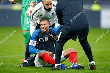 France's Kylian Mbappe grimaces after jumping over Uruguay goalkeeper Martin Campana during the international friendly soccer match between France and Uruguay at the Stade de France stadium in Saint-Denis, outside Paris, Tuesday, Nov.20, 2018