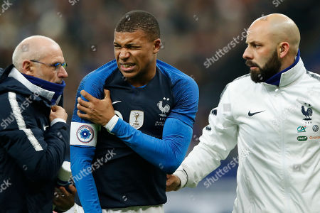 France's Kylian Mbappe holds his shoulder after falling following jumping over Uruguay goalkeeper Martin Campana during the international friendly soccer match between France and Uruguay at the Stade de France stadium in Saint-Denis, outside Paris, Tuesday, Nov.20, 2018