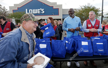 A man holds a pie he received while Charlotte Hornets owner Michael Jordan Michael Jordan greets people and hands out food for Thanksgiving to members of the community in Wilmington, N.C