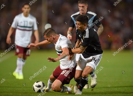 Mexico's Jesus Duenas, left, fights for the ball with Argentina's Maximiliano Meza during a friendly soccer match in Mendoza, Argentina