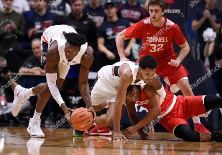 Stock Photo of Connecticut's Kassoum Yakwe, left, picks up a loose ball after Connecticut's Jalen Adams and Cornell's Troy Whiteside, bottom right, become tangled as Cornell's Jack Gordon, back, looks, during the first half of an NCAA college basketball game, in Hartford, Conn