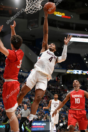 Connecticut's Jalen Adams (4) goes up for a basket as Cornell's Jack Gordon (32) and Matt Morgan (10) defend during the second half of an NCAA college basketball game, in Hartford, Conn