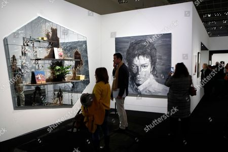 """Visitors watch """"The Whiz"""" (2012), left, by US artist Rashid Johnson and """"In Memory of Michael Jackson"""" (2017), center, by Chinese-born artist Yan Pei-Ming as part of the exhibition Michael Jackson on the Wall at the Grand Palais museum in Paris, Wednesday, Nov.21, 2018. The exhibition displays artists art pieces inspired by Michael Jackson's songs, choreographies and video clips"""