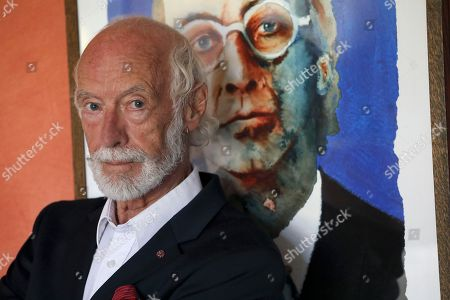 Portrait of Roger McGough standing in front of younger painting of himself, in his home