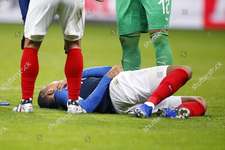 An injured France's foreward Kylian Mbappe lies on the field after being tackled by Uruguay's goalkeeper Martin Campana