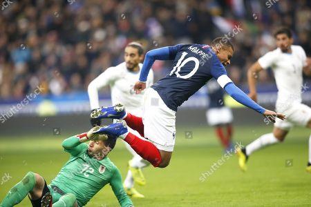 France's foreward Kylian Mbappe is tackled by Uruguay's goalkeeper Martin Campana (bottom)