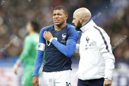 An injured Kylian Mbappe grimaces as he leaves the field after being tackled by Uruguay's goalkeeper Martin Campana