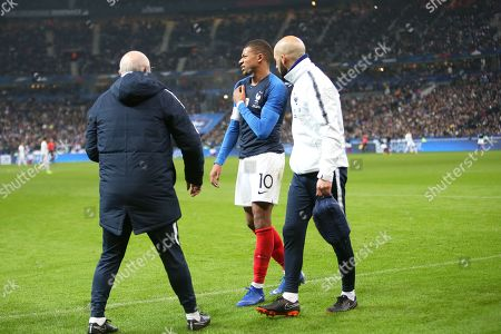 An injured Kylian Mbappe (C) reacts as he leaves the field after being tackled by Uruguay's goalkeeper Martin Campana
