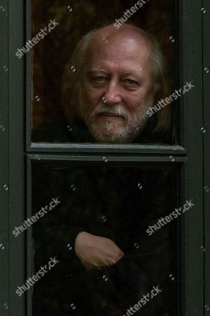 Laszlo Krasznahorkai poses for a portrait behind a window