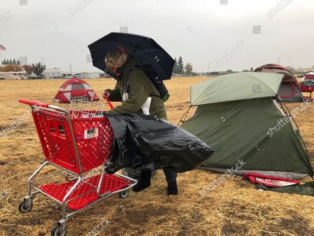 Amy Sheppard packs up items outside her tent in a Walmart parking lot in Chico, Calif., that's been a makeshift campground for people displaced by wildfire, Wednesday morning, . Sheppard lost her home in Magalia to the Camp fire. She was staying in the tent for four days with her sister and 1-year-old niece. They are moving to a motel because of rain that began Wednesday
