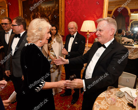 Camilla Duchess of Cornwall is greeted by Lord Jeffrey Archer at the Julien MacDonald Fashion Show Reception at Lancaster House in London, which is supporting the National Osteoporosis Society charity.