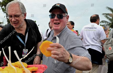 The special envoy of the European Union for Peace Eamon Gilmore (C) takes a piece of pineapple during his visit to the Territorial Space for Training and Reintegration (ETCR) in La Montanita in Caqueta, Colombia, 21 November 2018. The representatives visited the department of Caqueta to learn about two of the development projects sponsored by the organization.