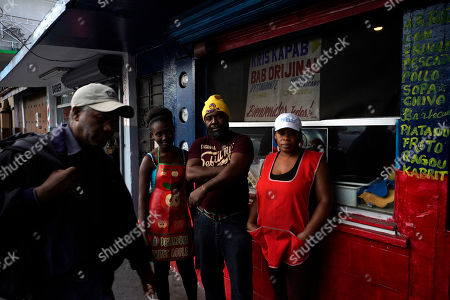 Stock Picture of Haitian immigrant Wilthene Pierre poses for a photo with two of his cooks Emily, left, and Violette Novembre, in front of the Kriskapab Baborijinal Haitian restaurant in Tijuana, Mexico, . The bright blue and red cafe serves Mexicans and Haitians dishes of coconut rice, mashed plantains and goat stew