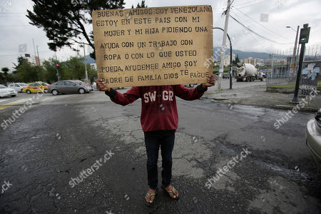 """Jose Perez holds a sign that reads in Spanish """"Good afternoon, I am Venezuelan. I am in this country with my wife and daughter asking for help. A job, clothing, or with anything you can. Please help. I am a father. May God repay you,"""" at a street corner in Quito, Ecuador, . According to the United Nations, over three million Venezuelans have migrated in recent years"""