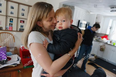 Anna Ford hugs her son Eli as he arrives home from nursery school with Ford's partner, Sara Watson, background, in the village of Saunderstown, in Narragansett, R.I. Three years after the landmark U.S. Supreme Court case that gave same-sex couples the right to marry nationwide, a patchwork of outdated state laws governing who can be a legal parent presents obstacles for many LGBTQ couples who start a family, lawyers say