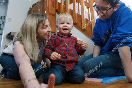 Stock Image of Anna Ford, left, and her partner, Sara Watson, play with their son Eli at home in the village of Saunderstown, in Narragansett, R.I. Three years after the landmark U.S. Supreme Court case that gave same-sex couples the right to marry nationwide, a patchwork of outdated state laws governing who can be a legal parent presents obstacles for many LGBTQ couples who start a family, lawyers say