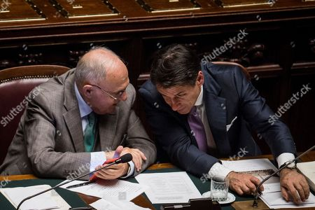 Italian Prime Minister Giuseppe Conte (R) gives a statement on Italian budget to the Chamber of Deputies next to Minister for European Affairs, Paolo Savona