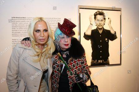 Donatella Versace and Anna Piaggi pose next to a Richard Avedon photo