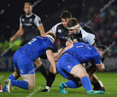 Rhodri Jones of Ospreys is tackled by James Tracy, left, and Peter Dooley of Leinster