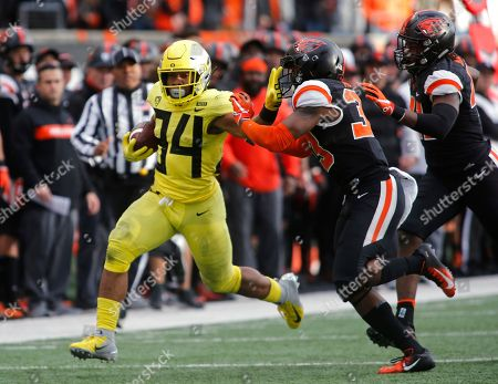 Stock Picture of Oregon running back C.J. Verdell (34) tries to stiff-arm Oregon State safety Jalen Moore (33) on a run during the second half of an NCAA college football game in Corvallis, Ore., . Oregon won 55-15