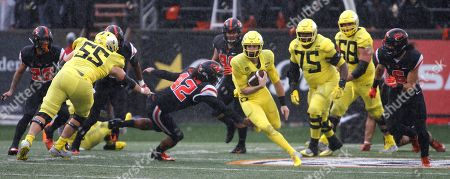 Stock Picture of Oregon quarterback Braxton Burmeister, center right, gets past Oregon State linebacker Doug Taumoelau (42) in the second half of an NCAA college football game in Corvallis, Ore