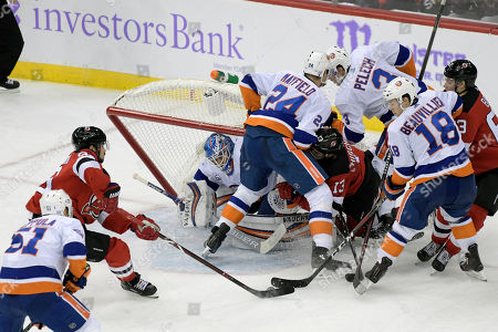 New York Islanders' Adam Pelech (3) checks New Jersey Devils' Nico Hischier (13) into the back of the net as it falls onto Islanders goaltender Thomas Greiss (1) and Scott Mayfield (24) during the third period of an NHL hockey game, in Newark, N.J. The Islanders won 4-3 in overtime
