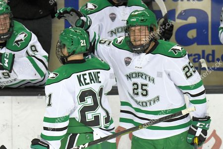 North Dakota Fighting Hawks forward Joel Janatuinen (25) congratulates North Dakota Fighting Hawks forward Jackson Keane (21) after he scored his first collegiate goal during a NCAA men's college hockey game between the Alaska Anchorage Seawolves and the University of North Dakota Fighting Hawks at Ralph Engelstad Arena in Grand Forks, ND. North Dakota won 5-2