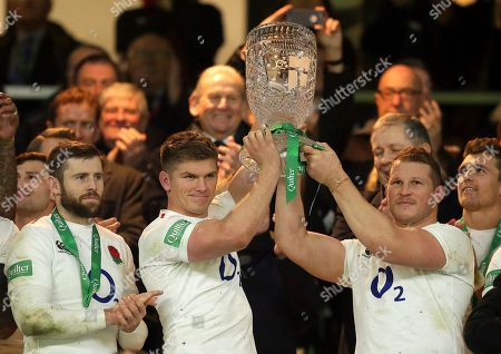 England's Owen Farrell, second left, and England's Dylan Hartley hold up the Cook Cup after the rugby union international between England and Australia at Twickenham in London, . England won the match 37-18