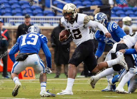 Wake Forest Quarterback Jamie Newman (12) carries the ball ahead of Duke's Jordan Hayes (13) during the first half of an NCAA college football game in Durham, N.C