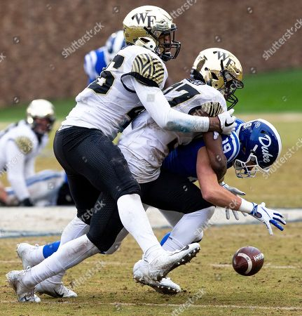 Duke's Jake Bobo (19) fumbles the ball after making a catch as Wake Forest's Nasir Greer, middle, and DJ Taylor, left, move in for a tackle during the second half of an NCAA college football game in Durham, N.C