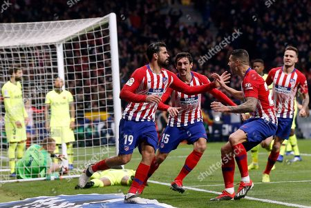 Xavi Hernandez. Atletico's Diego Costa, center, celebrates after scoring the opening goal during a Spanish La Liga soccer match between Atletico Madrid and FC Barcelona at the Metropolitano stadium in Madrid