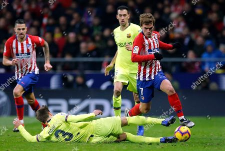 Xavi Hernandez. Barcelona's Gerard Pique tackles Atletico's Antoine Griezmann, right, during a Spanish La Liga soccer match between Atletico Madrid and FC Barcelona at the Metropolitano stadium in Madrid
