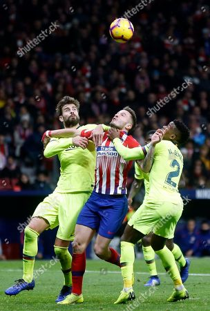Xavi Hernandez. Atletico's Saul Niguez fights for the ball with Barcelona's Gerard Pique and Nelson Semedo, right, during a Spanish La Liga soccer match between Atletico Madrid and FC Barcelona at the Metropolitano stadium in Madrid